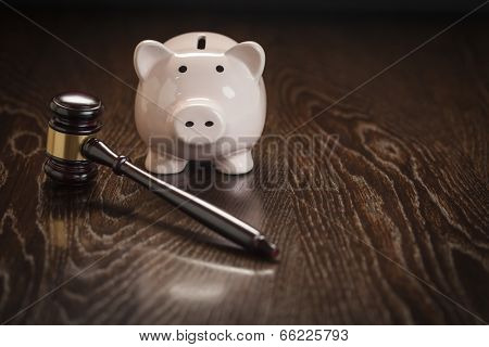 Gavel and Piggy Bank on Wooden Table.