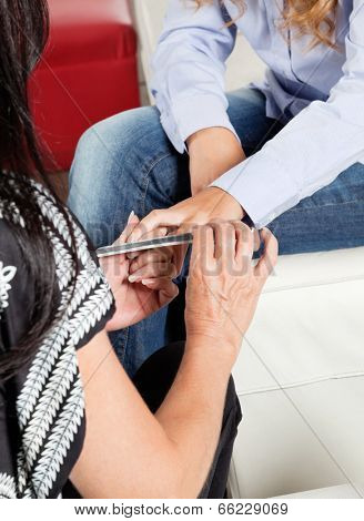 Midsection of manicurist filing client's nail at beauty parlor