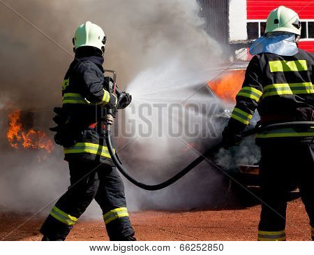 The firemans are extinguish a exploded burning car