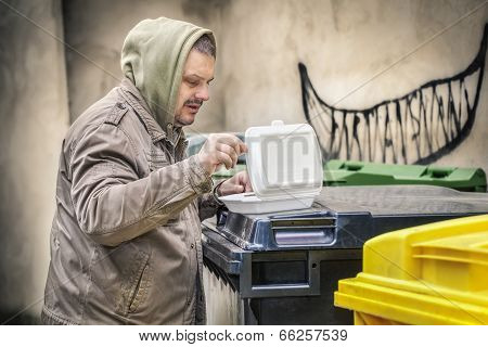 Homeless man near garbage container with food box