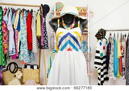 Wardrobe with summer clothes nicely arranged and a beach outfit on a mannequin.