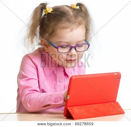 kid in glasses looking at mini tablet pc screen sitting at table