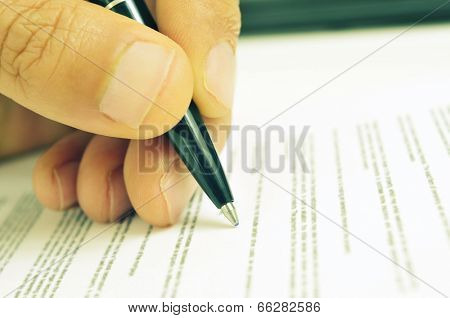 closeup of the hand of a man ready to sign a document with a pen, with a retro filter effect