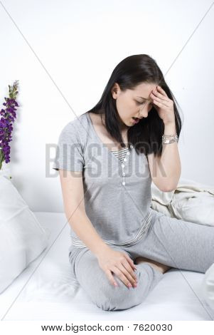 Woman With Headache In Bed