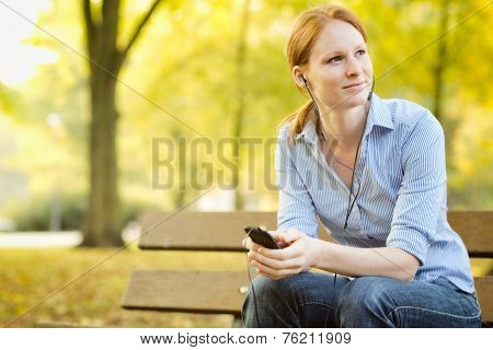 Casual Woman Listening To Music In A Park