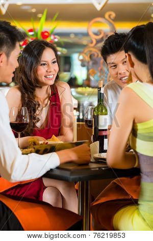 Four Asian Chinese business people having dinner in elegant club restaurant or hotel