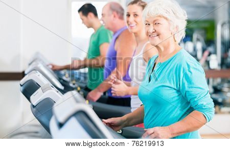 Group with senior and young men and women people on treadmill in fitness gym running for sport