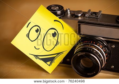 Drawn smiley face on a post-it note sticked on photo camera