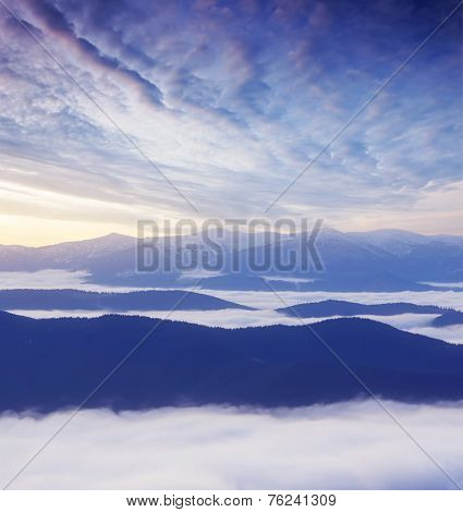 Autumn landscape with morning fog in the mountains. Predawn twilight. Half an hour before sunrise. Carpathian mountains, Ukraine, Europe