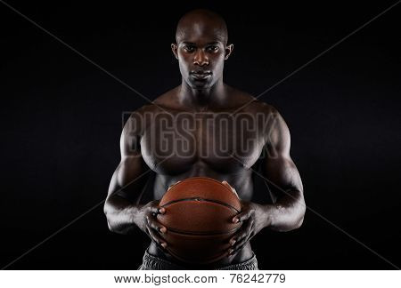 Portrait of muscular young man shirtless holding a basketball. Afro american basketball player against black background. poster