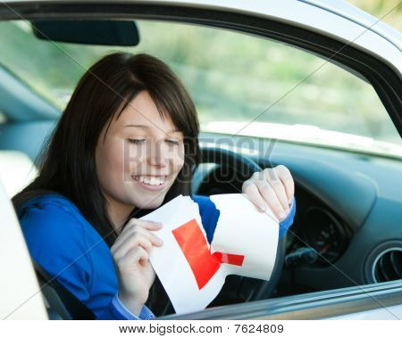 Brunette Teen Girl Sitting In Her Car Tearing A L-sign