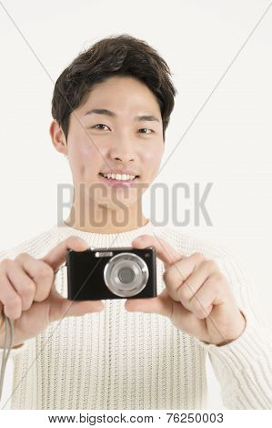Asian young man with digital camera