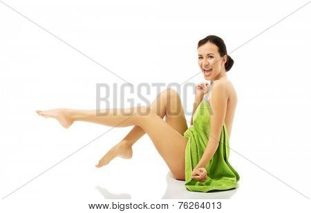 Laughing woman wrapped in towel with legs up.