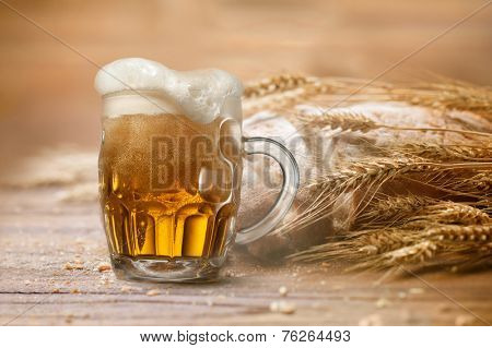 Glass of beer with wheat and bread on wooden background
