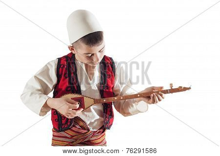 young boy playing traditional string instrument