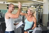 Smiling male trainer giving high five to his client on exercise bike at gym poster