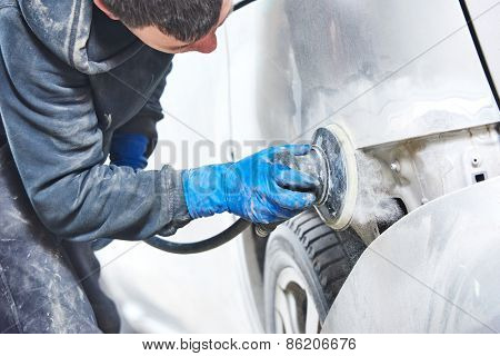 mechanic worker repairman sanding polishing car body and preparing automobile for painting during repair and renew at service station shop