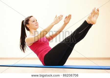 young female instructor doing stretching pilates exercises in sport club