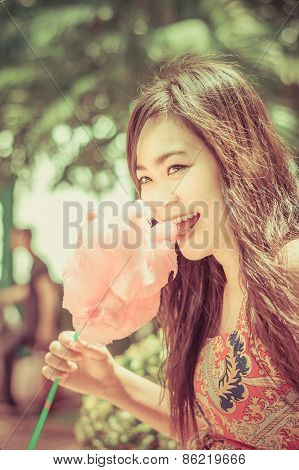 Cute Thai Girl Is Eating Pink Candyfloss With Joy In Vintage Color.