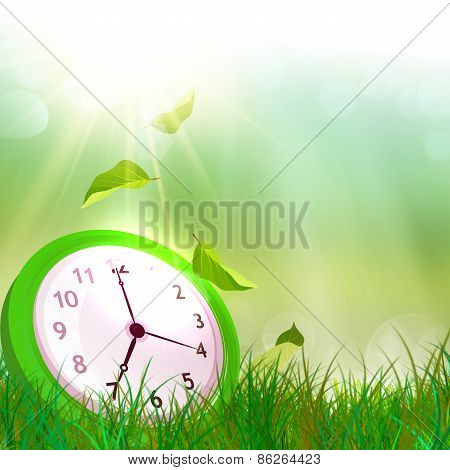 Alarm clock on the green grass. Summer time.