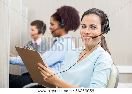 Portrait of smiling female customer service representative writing on clipboard with colleagues working in background at call center