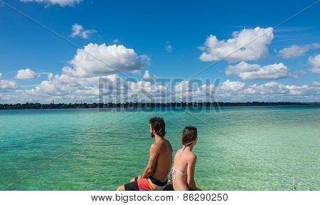 Beautiful Couple In Love Looking At Tranquil Bacalar Lake. Riviera Maya, Mexico. Tropical Travel.