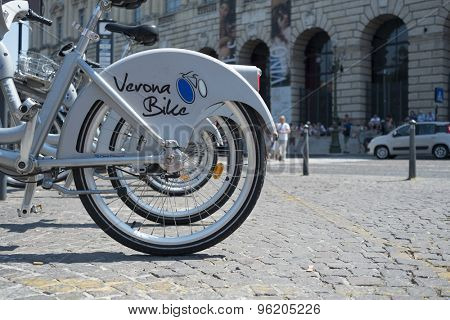 VERONA, ITALY - JULY 11: Cropped low angle shot of line of rental bikes . July 11, 2015 in Verona.
