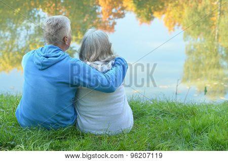 Senior couple sitting near lake