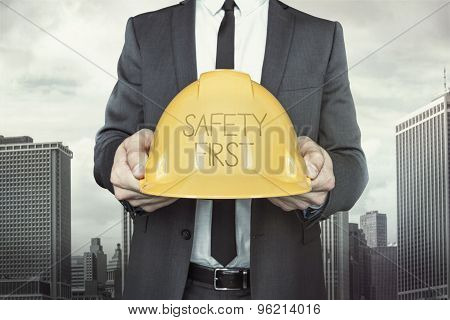Safety first text on helmet what businessman is holding
