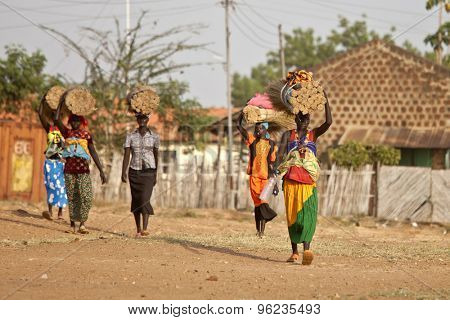 TORIT, SOUTH SUDAN-FEBRUARY 20, 2013: Unidentified women carry heavy loads on their heads in the village of Torit, South Sudan