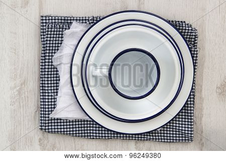 Vintage enamelware crockery on cloths on wooden background poster