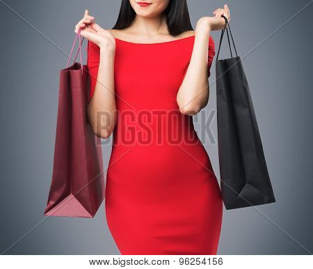 Beautiful Brunette Woman In A Red Dress Is Holding Fancy Shopping Bags. Grey Background.
