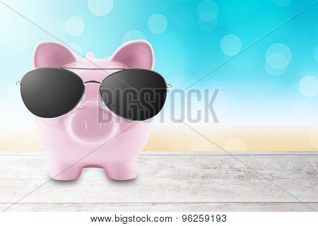 summer piggy bank with sun glasses on the beach