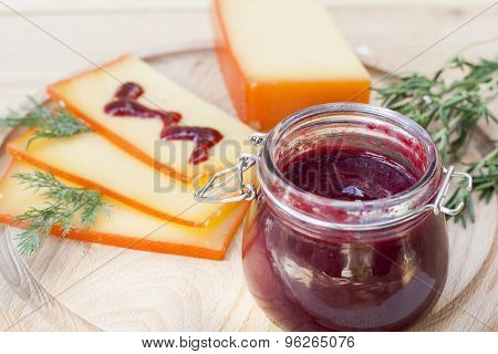 Sliced cheese and cherry sauce on a wooden board with dill and rosemary