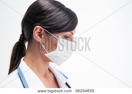 Side view portrait of a pensive female medical doctor in mask isolated on a white background