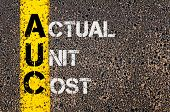 Concept image of Business Acronym AUC as Actual Unit Cost written over road marking yellow paint line. poster
