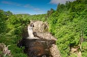 High Force Waterfall on a sunny day viewed from the south bank of the River Tees on the Pennine Way in woodland poster