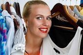 Beautiful smiling blonde woman standing inside wardrobe rack full of clothes happy to have it. Shopping and consumerism or stylist concept. Nothing to wear and hard to decide concept poster