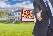 Real Estate Agent Reaches for Handshake with Sold Sign and New House Behind. poster