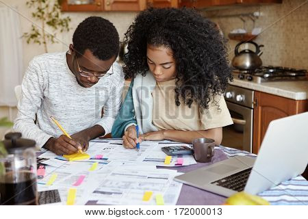 African Man In Glasses And Woman With Curly Hair Having Concentrated Looks While Busy Working Throug