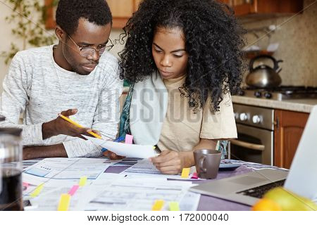 Indignant African Husband Gesturing With Pencil, Reproaching His Wife For Doing Mistake While Calcul