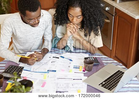 African Couple Facing Financial Problem. Stressed Female With Afro Hairstyle Clasping Hands, Looking