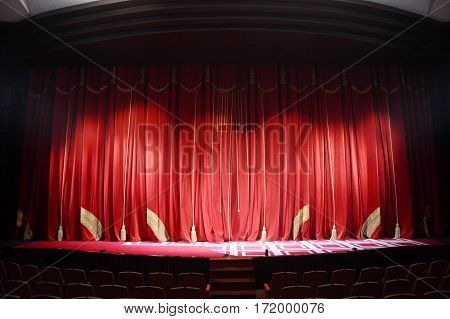 red theater curtain with embroidery stretched on a scene of theatre