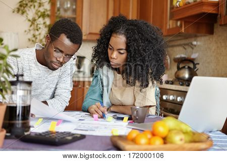 Indoor Shot Of Young African Family Analyzing Their Finances, Planning Budget, Accounting Domestic E