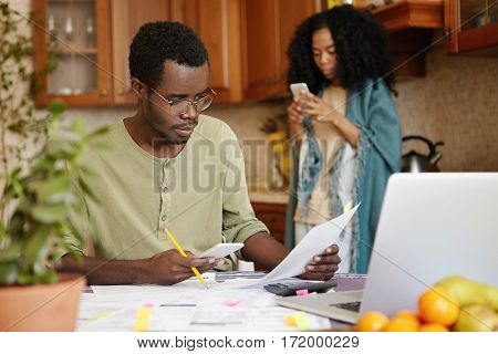 Serious And Concentrated Young African-american Male Wearing Spectacles Paying Bills Online, Using B