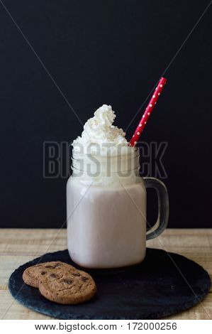 Vertical background with hot chocolate topped with whipped cream and red straw served on a trendy black slate board with two chocolate cookies