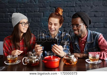 Cheerful Redhead Caucasian Student Girl Holding Black Digital Tablet Sitting Between Her Two Best Fr