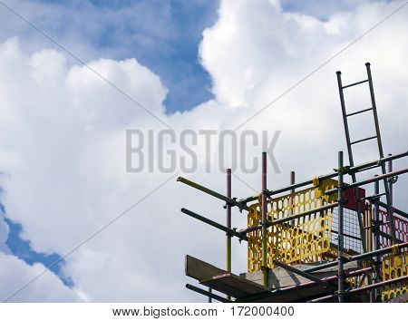 Telephoto view of builders scaffolding against cloudy sky.
