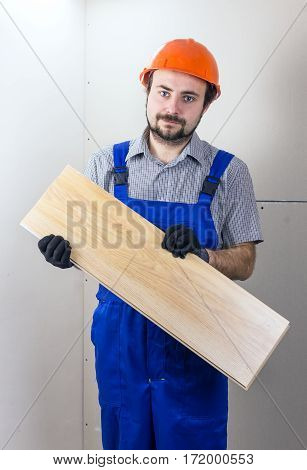 Construction worker with laminated floorboard in a protective helmet