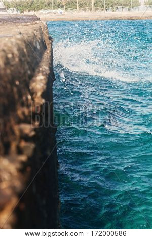 The Waves Strike The Stone Pier In Blurring
